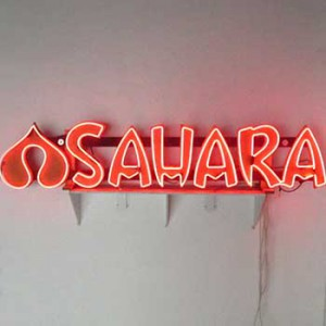 SAHARA red neon mounted to gold cut-out letters