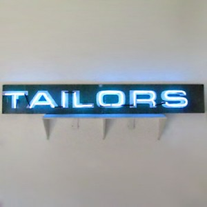 TAILORS blue neon above white lettering on aged chalkboard-green wood